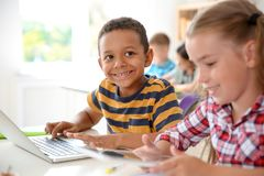 Cute little children with gadgets sitting at desk. In classroom. Elementary school royalty free stock photos