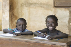 Cute Little Children Learning with Pens and Paper in Africa Sch. Ooling Education Symbol stock photo