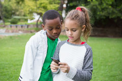 Cute little children looking at smartphone Royalty Free Stock Images