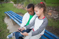 Cute little children looking at smartphone Royalty Free Stock Photography