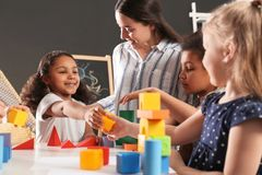 Cute little children and nursery teacher playing with building blocks in kindergarten. Indoor activity royalty free stock photos
