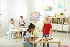 Cute little children painting at lesson. Indoors royalty free stock photography