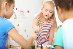 Cute little children painting at lesson. Indoors stock image