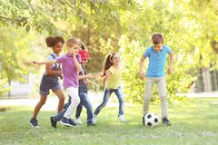 Cute little children playing with ball outdoors. On sunny day stock photo