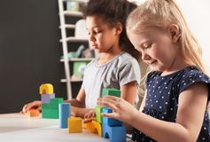 Cute little children playing with building blocks in kindergarten royalty free stock photos