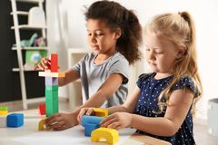 Cute little children playing with building blocks in kindergarten. Indoor activity royalty free stock image
