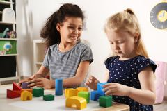 Cute little children playing with building blocks in kindergarten. Indoor activity royalty free stock photography