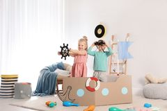 Cute little children playing with cardboard ship stock images
