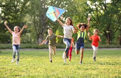 Cute children playing with kite outdoors on sunny day stock images