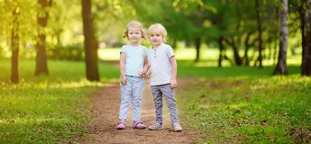 Cute little children playing together and holding hands in sunny royalty free stock photography
