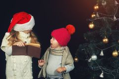 Cute little children reading a book by the Christmas tree Royalty Free Stock Photography