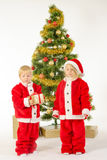 Cute little children share christmas gifts near tree Royalty Free Stock Image