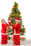Cute little children share christmas gifts near tree Royalty Free Stock Photo
