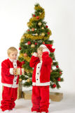 Cute little children share christmas gifts near tree Stock Photos