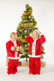 Cute little children share christmas gifts near tree Royalty Free Stock Images