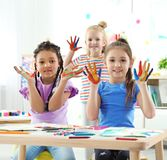 Cute little children showing painted hands at lesson indoors stock image