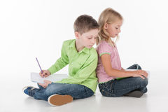 Cute little children sitting on floor and drawing. Small boy looking over girl shoulder Stock Images