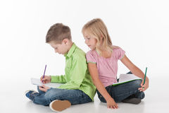 Cute little children sitting on floor and drawing. Small girl and boy drawing picture Royalty Free Stock Images