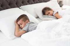 Cute little children sleeping in bed stock image