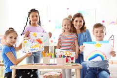 Cute little children with teacher showing their paintings at lesson stock image