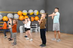 Cute little children and trainer doing physical exercise in school gym. Healthy lifestyle royalty free stock photo