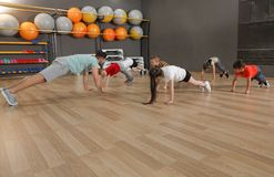 Cute little children and trainer doing physical exercise in school gym. Healthy lifestyle royalty free stock image