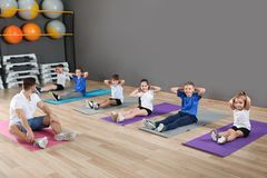Cute little children and trainer doing physical exercise in school gym. Healthy lifestyle stock image