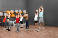 Cute little children and trainer doing physical exercise in school gym. Healthy lifestyle stock photography