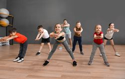 Cute little children and trainer doing physical exercise in school gym. Healthy lifestyle stock photo