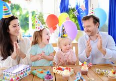 Cute little children twins and their parents having fun and celebrate birthday party with colorful decoration Stock Photos