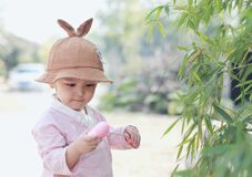 Lovely chinese Baby girl With a hat play on front of the bamboo stock photos