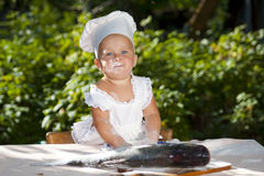 Cute little cook and big fish. Cute little girl in cook hat with the face and hands in the flour prepared fish stock photo