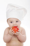 Cute little cook eating apple Royalty Free Stock Photo