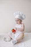 Cute little cook eats tomato Stock Images