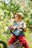 Cute little country boy sitting in a garden Royalty Free Stock Photography