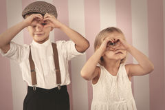 Cute little couple. Kids looking through the heart shape from hands stock images
