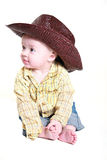 Cute little cowboy. Little cowboy sitting on the floor playing with his toes Royalty Free Stock Photography