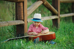 Cute little cowboy playing guitar royalty free stock photography