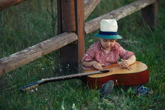 Cute little cowboy playing guitar royalty free stock images