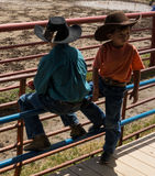 Cute little cowboys at a rodeo in colorado. Young lads perched on a railing at an annual round-up in the summertime stock image