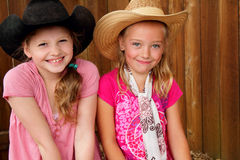 Cute little cowgirls. Happy expression of two cute little blond farm girls in pink shirst and cowboy hats. Shallow depth of field Stock Photos