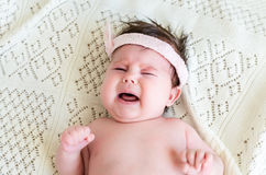 Cute little crying newborn baby girl seeking attention. With crying and screaming, wearing in pink head bandage bow on her head on the background of woolen Royalty Free Stock Image
