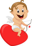 Cute little Cupid with bow sitting on heart Royalty Free Stock Photo