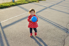 Cute little curly baby girl with ball in her hands on the stadium Royalty Free Stock Image