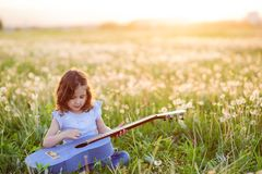 Cute little curly caucasian girl playing guitar sitting on green grass in summer bloom field