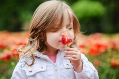 Cute little curly hair blonde girl smelling a tulip. On flower background at park royalty free stock image