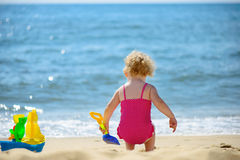 Cute little curly haired girl playing with sand Royalty Free Stock Images