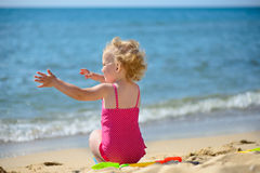 Cute little curly haired girl playing with sand Royalty Free Stock Image