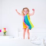 Cute little curly toddler girl jumping on white bed stock photos