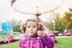 Cute little daughter blowing bubbles, amusement park, fun fair. Cute little daughter blowing bubbles, family in amusement park, fun fair royalty free stock images
